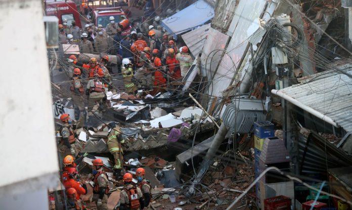 #Pracegover Foto: na imagem há escombros, pessoas e fios