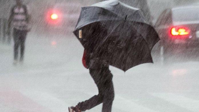 #Pracegover Na foto, pessoa caminhando sob chuva forte segurando um guarda-chuva