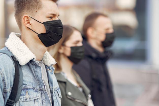 #Pracegover Na foto, pessoas na rua usando máscara