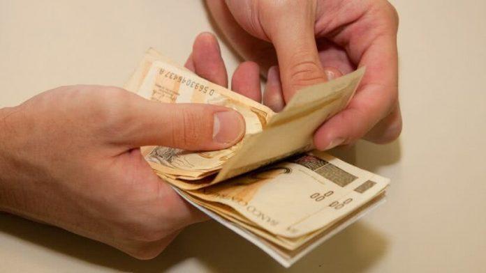#Pracegover Na foto, homem segurando dinheiro