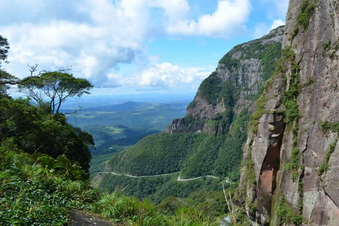 #Pracegover Foto: na imagem há rochas, árvores e via