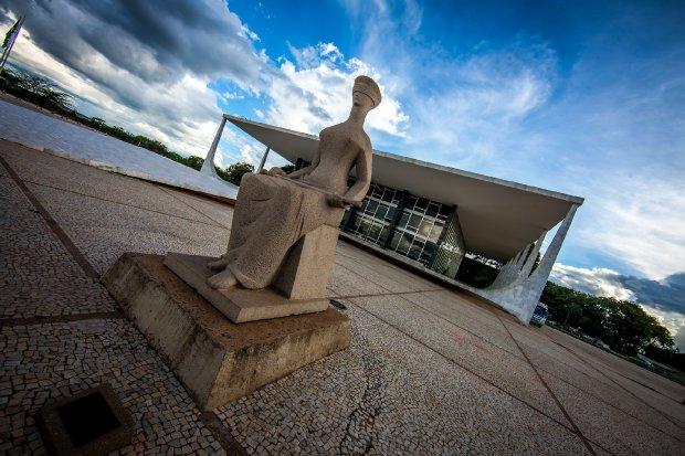 #Pracegover Foto: na imagem há uma estátua e um prédio