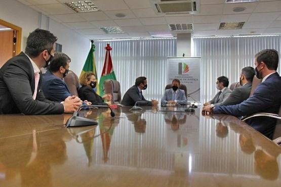 #Pracegover Foto: na imagem há pessoas, uma mesa e bandeiras