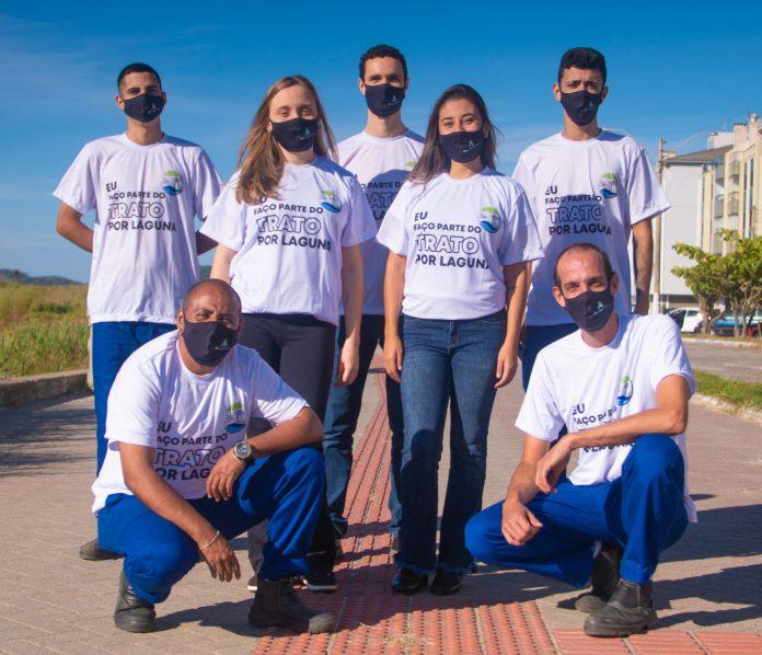 #Pracegover Foto: na imagem há algumas pessoas com calça azul e camiseta branca