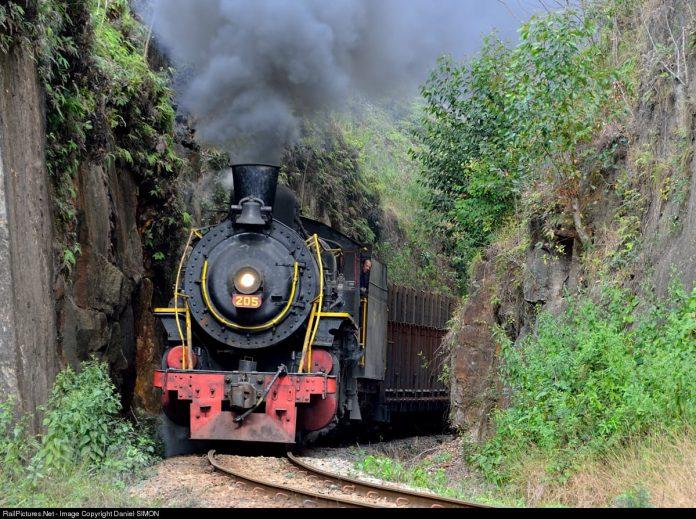 #Pracegover Foto: na imagem há um trem, área verde e rochas