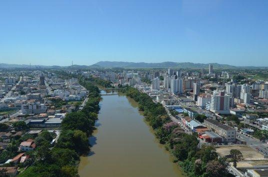 #Pracegover Na foto, rio cercado por árvores e construções