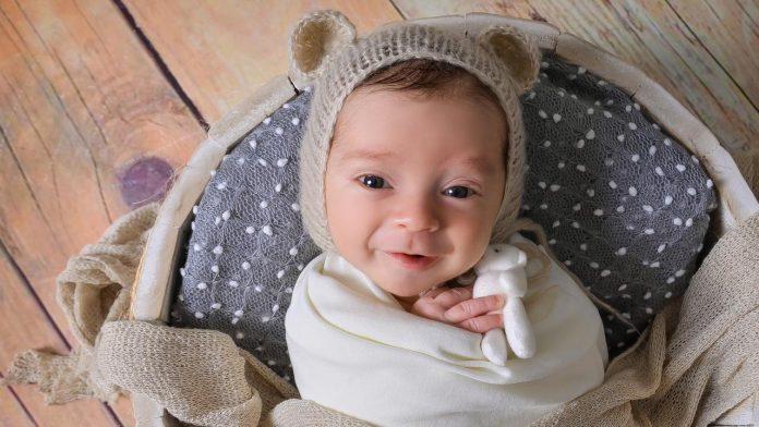 #Pracegover Na foto, bebê com uma touca e enrolado em uma pano de cor clara
