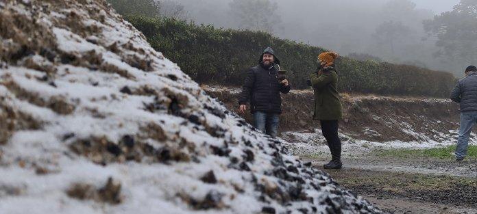 #Pracegover Na foto, detalhe para neve sobre as pedras e o morro e ao fundo um casal