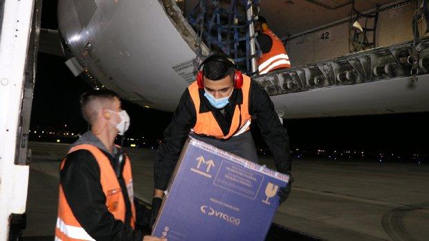 #Pracegover Na foto, homens tirando caixas de um compartimento de um avião