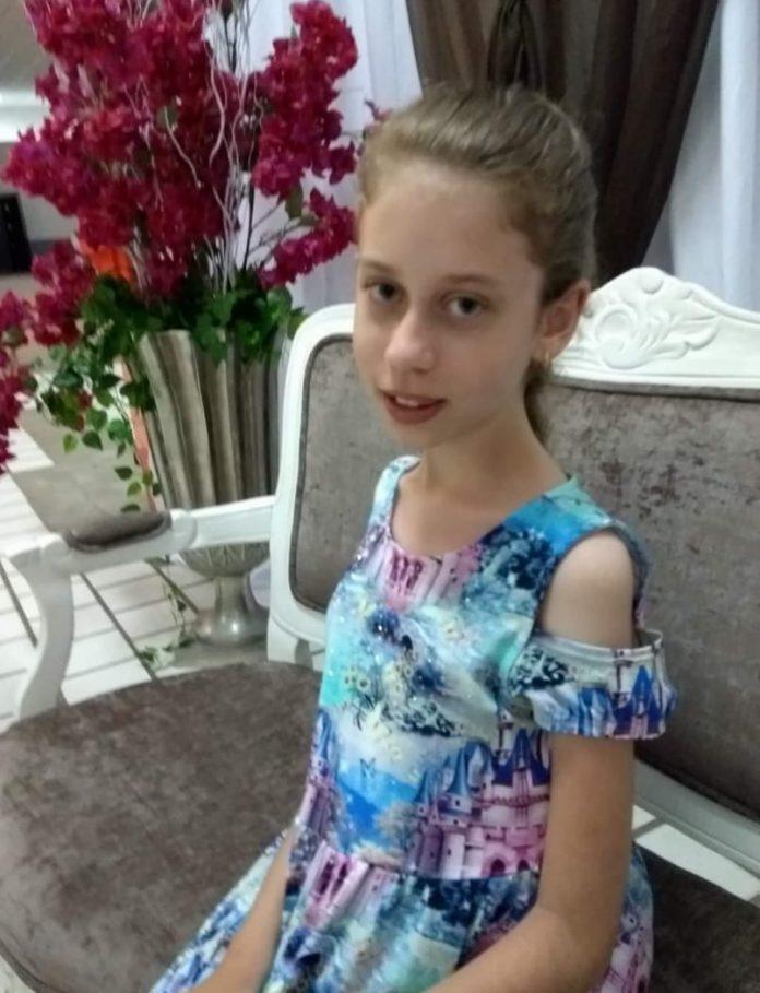 #Pracegover foto: na imagem há uma menina sentada em um sofá e um vaso de rosas vermelhas
