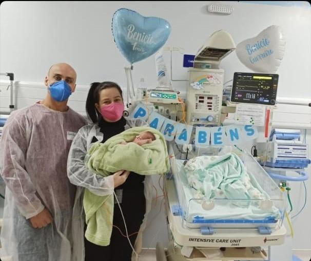 #Pracegover Foto: na imagem há uma mulher com um bebê no colo, um homem, um berço e balões