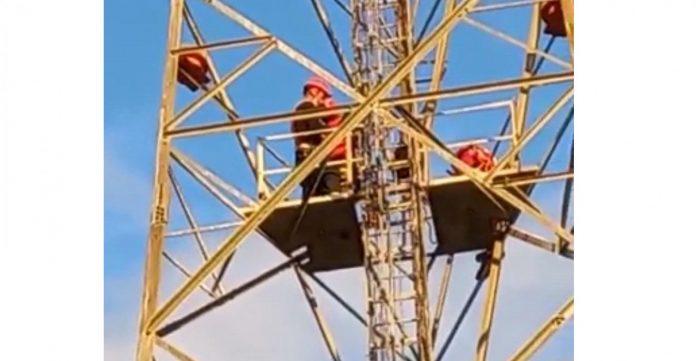 #Pracegover Na foto, homens em cima de uma torre de telefonia