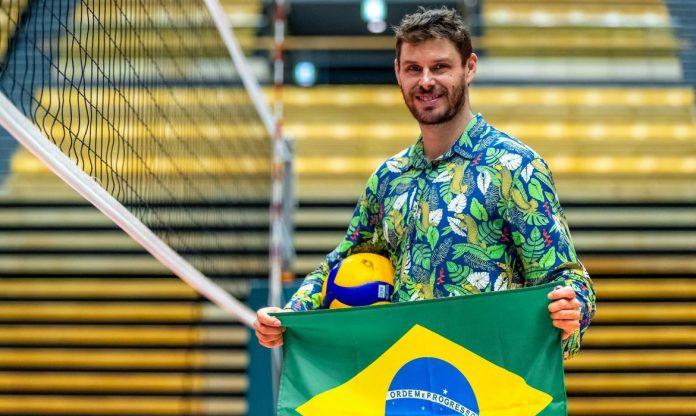 #Pracegover Foto: na imagem há um homem, uma bola, a bandeira do Brasil, uma rede de vôlei e arquibancada