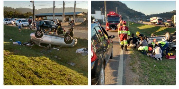 #Pracegover Na foto, Bombeiros atendendo vítimas em um carro capotado