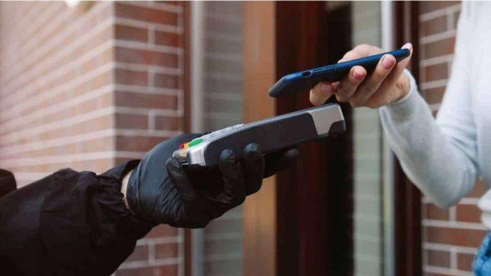 #Pracegover Na foto, homem segurando uma máquina de cartão e uma mulher efetuando pagamento