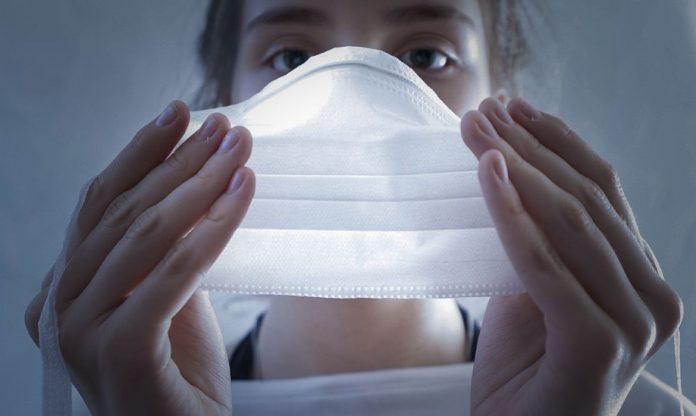 #Pracegover Na foto, mulher colocando uma máscara sobre o rosto