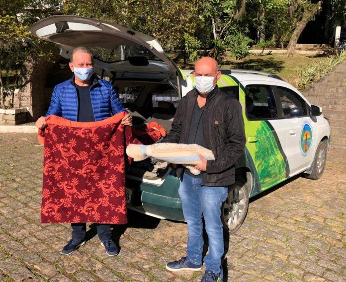 #Pracegover Foto: na imagem há dois homens, carros e árvores