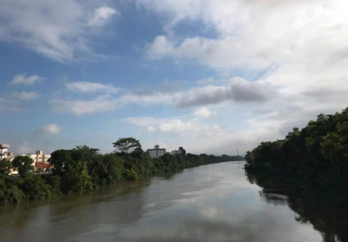 #Pracegover Na foto, céu parcialmente coberto por nuvens, rio com águas calmas e vegetação nas margens