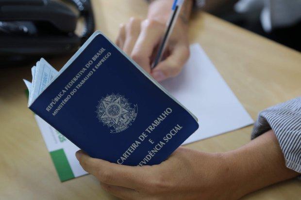#Pracegover Foto: na imagem há duas mãos, uma caneta, uma folha e carteira de trabalho