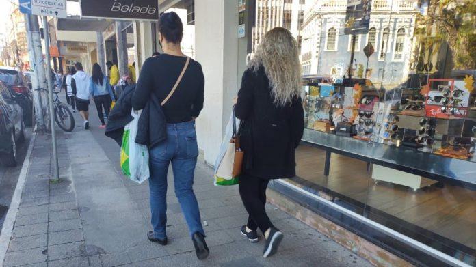 #Pracegover Na foto, pessoas caminhando no centro comercial de Tubarão