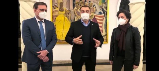 #Pracegover Foto: na imagem há três pessoas de máscara e um quadro