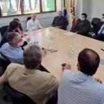#Pracegover Na foto, pessoas reunidas em volta de uma mesa