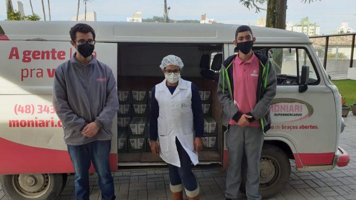 #Pracegover Na foto, funcionários do mercado que fizeram a entrega e uma representante do asilo