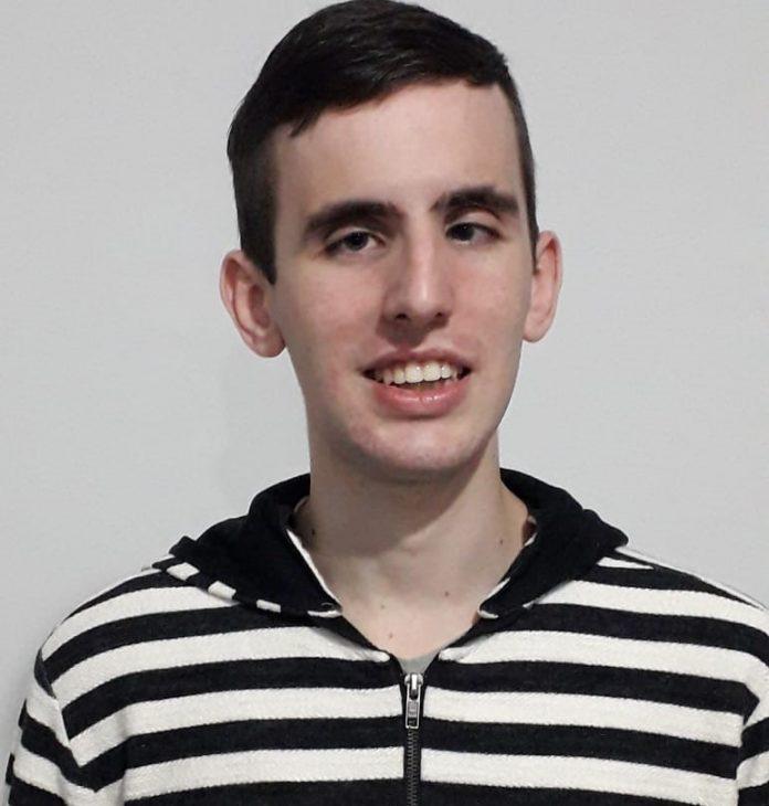 #Pracegover Foto: na imagem há um jovem com camisa listrada em preto e branco