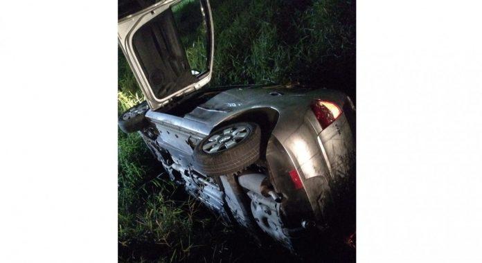 #Pracegover Na foto, carro caído sobre matagal