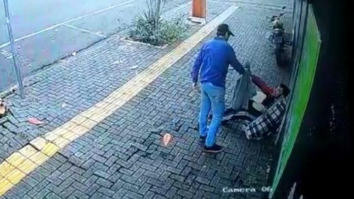 #Pracegover Na foto, homem entregando um casaco a um morador de rua