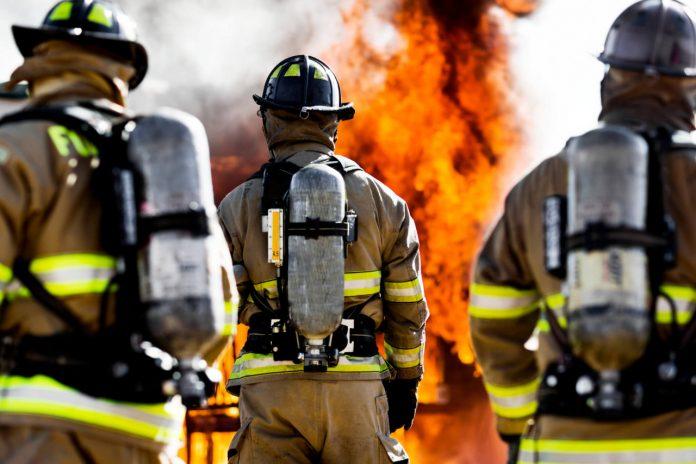 #Pracegover Foto: na imagem há três homens e chamas