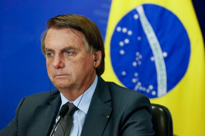 #Pracegover Foto: na imagem há um homem de terno e a bandeira do Brasil