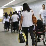 #Pracegover Na foto, cadeirante acompanhando pessoas em um corredor