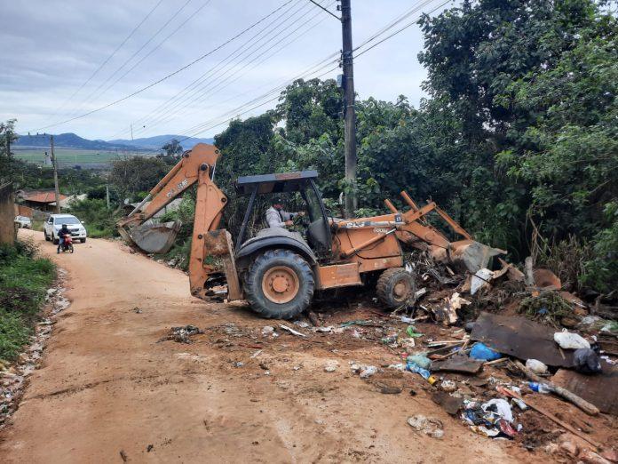 #Pracegover Foto: na imagem há uma máquina, árvores , estrada e entulhos