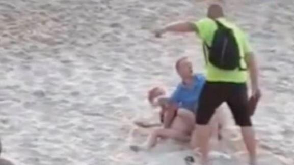 #Pracegover Na foto, homem agride casal deitado na areia