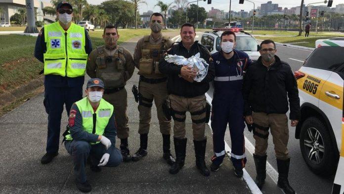 #Pracegover Na foto, policiais segurando um bebê