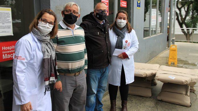 #Pracegover Na foto, pessoas ao lado de equipamentos para hospital