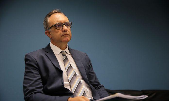 #Pracegover Na foto, Maurício Cunha está sentado e com um semblante sério