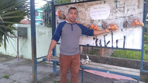 #Pracegover Na foto, homem segurando uma fruta