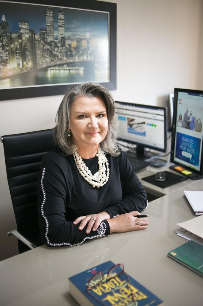 #Pracegover Foto: na imagem há uma mulher, uma cadeira, mesa, computador, folhas e um livro