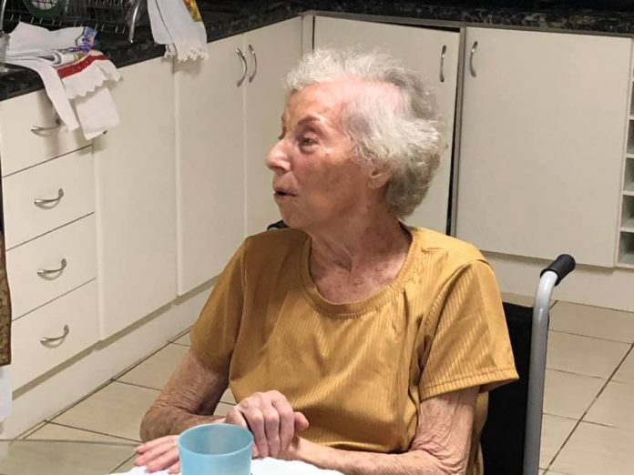 #Pracegover Foto: na imagem há uma idosa, móveis, utensílios domésticos e eletrodomésticos