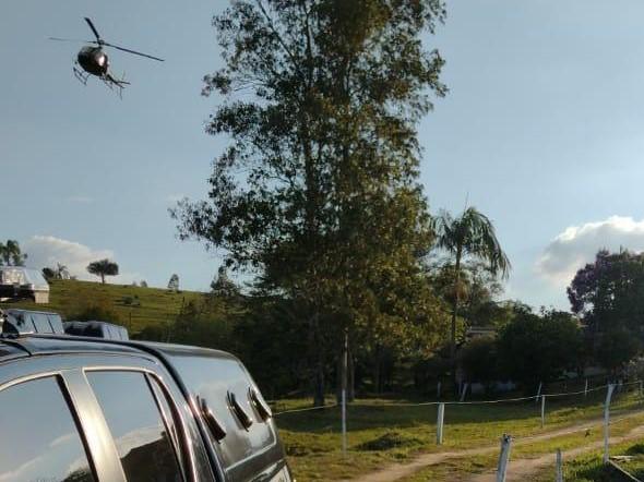 #Pracegover Na foto, helicóptero e viatura da polícia