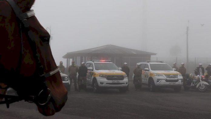 #Pracegover Na foto, policiais ao lado de viaturas em um dia de nevoeiro. Detalhe para imagem de um cavalo no canto esquerdo