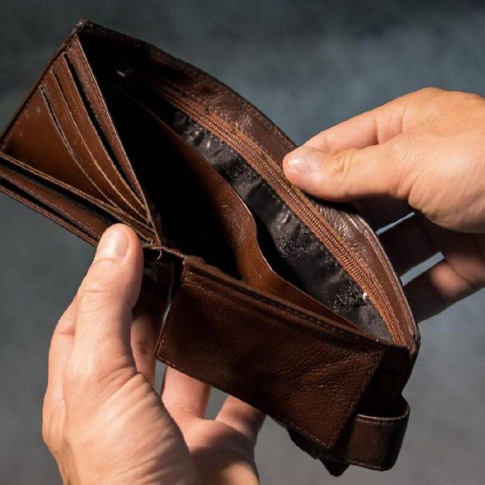 #Pracegover Na foto, homem segurando uma carteira vazia