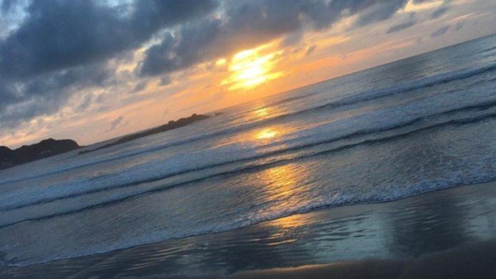 #Pracegover Na foto, nascer do sol no mar, céu parcialmente coberto de nuvens