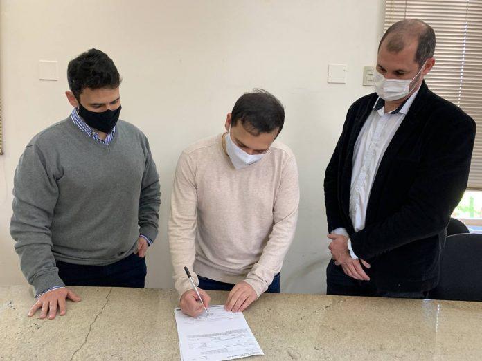 #Pracegover Foto: na imagem há três pessoas e uma delas assinando papel