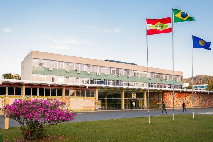 #Pracegover Foto: na imagem há um prédio, bandeiras, flores e gramado