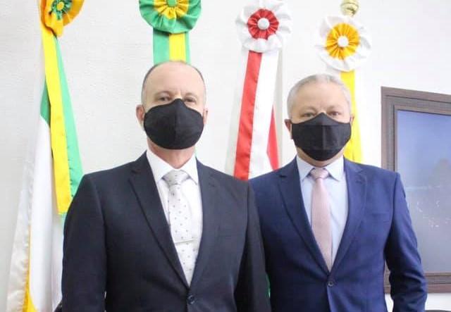 #Pracegover Foto: na imagem há dois homens e quatro bandeiras