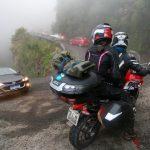 #Pracegover Foto: na imagem há carros, duas pessoas em uma moto, uma via e árvores