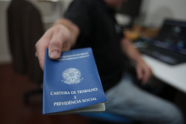#Pracegover Na foto, homem segurando uma carteira de trabalho